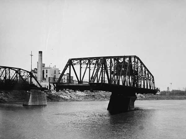 Redwood Bridge with visible overhead pilot cabin, swing span in operation, and Drewry Brewery in the background